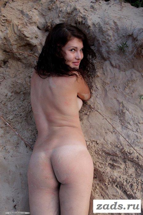 Голая красотка в лесу на песке.