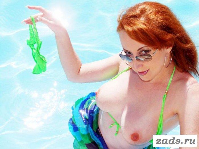 Рыженькая купается в бассейне в прозрачном купальнике (эротика)
