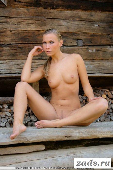 Девчонка шалит голая возле бревен