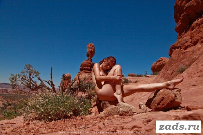 Голая девка жарится на красном песке