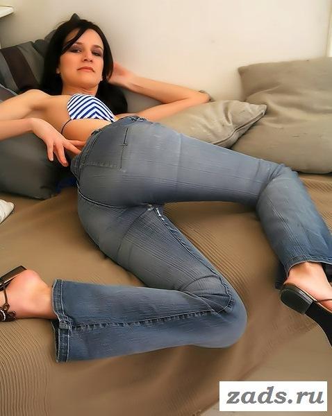 Медленно спускает джинсы брюнетка
