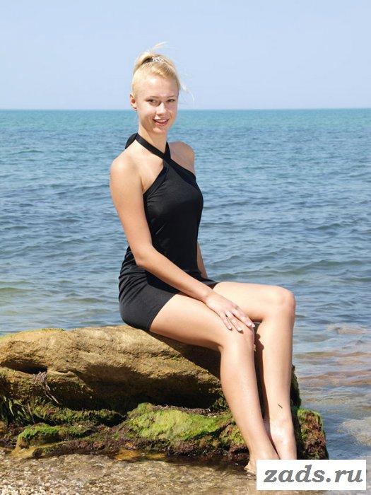 Снимает чёрное платье на берегу моря