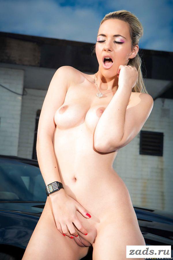 Сексуально позирует в сапогах у машины