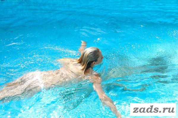 Стройная девушка плавает нагишом в эротических фото